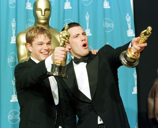 """LOS ANGELES, CA - MARCH 23: Oscar winners Matt Damon (L) and Ben Affleck hold the awards they won for best original screenplay for the film """"Good Will Hunting"""" which the two wrote during the 70th Annual Academy Awards 23 March in Los Angeles. (Photo credit should read HAL GARB/AFP/Getty Images)"""